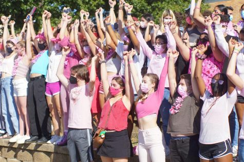 """PINK AND PROUD: Linking pinkies and shouting loudly, junior Maya Cidale sings the school song with her fellow classmates. Cidale is a transfer student, so this was her first pep rally at Mac, and she loved the spirit of the event. """"It was so cool to see everyone dressed in pink,"""" Cidale said. """"It showed support for breast cancer research, but it was also kind of a unifying factor as a student body."""" Cidale enjoyed the high energy atmosphere, despite the heat of the afternoon event. """"It was really hot outside and everyone was so sweaty,"""" Cidale said. """"But no one really cared because we were all having fun and the student leadership was so good about keeping us all engaged."""" Caption by Alice Scott."""