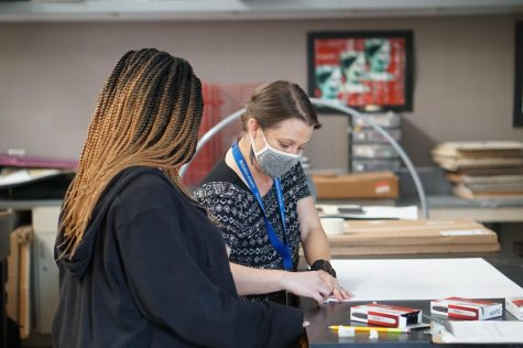 During her seventh-period Drawing 1 class on Aug. 31, art teacher Sarah Massey demonstrates to her students (including Olivia Ballard shown here) how to create the portfolio that they will use to hold all their drawings they create in the class.