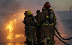 """Senior members of the LBJ Fire Academy line up to put out the propane fire at their first live fire skill day of the school year. Each person in the line has a specialized job, first in line holds the nozzle of the hose, the second and third are backup and the fourth person is the hose wrangler, making sure they have enough hose left to turn. """"We just had to learn every single job, and that was stressful,"""" senior and LBJ Fire Academy member Michael Valentino said. """"Every person has their job and they have to do it, and if you don't do it it's gonna go bad."""" Caption by Kennedy Weatherby."""
